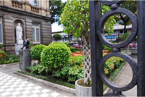 Showing slide 9 of 10 in image gallery, Iron gate with a garden pathway into the National Theater in San Jose,