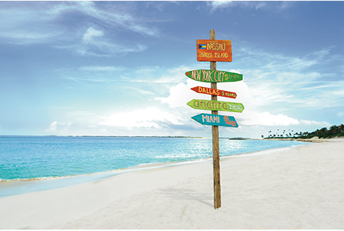Showing slide 9 of 25 in image gallery, Sign in the white sand in Nassau showing the distance to nearby cities