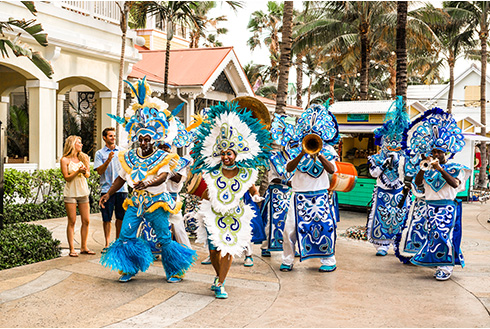 Showing slide 7 of 25 in image gallery, Festive dancers at Junkanoo wearing blue outfits
