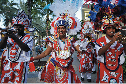 Showing slide 13 of 25 in image gallery, Festive dancers and musicians at Junkanoo wearing red outfits