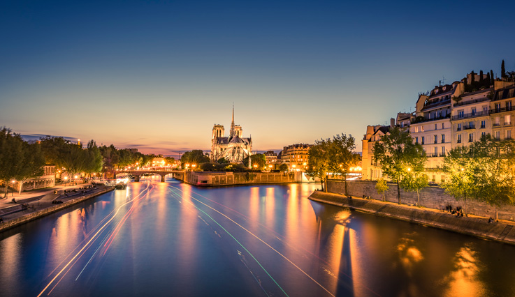 Showing slide 3 of 5 in image gallery, Seine riverfront with Notre-Dame Cathedral and boat light trails on the water at sunset in Paris, France.