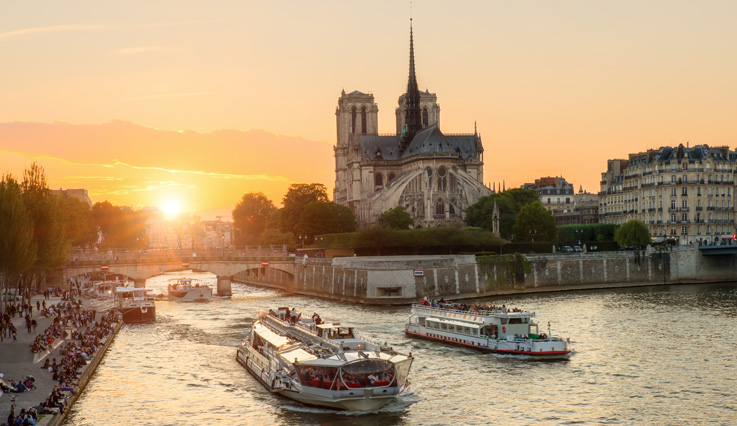 Showing slide 4 of 5 in image gallery, Sun settting over the Notre Dame de Paris cathedral
