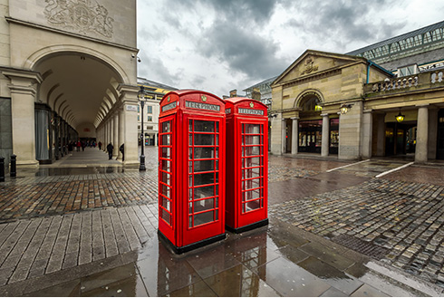 Showing slide 16 of 16 in image gallery, Two red telephone booths at Covent Garden Market on a rainy day