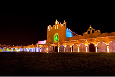 Showing slide 24 of 31 in image gallery, A building in Merida at night time with lights on