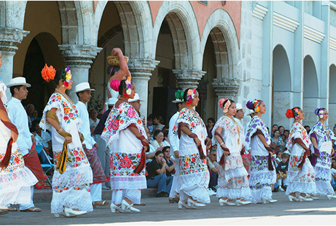 Showing slide 2 of 31 in image gallery, Traditional women dancing in dresses downtown Merida