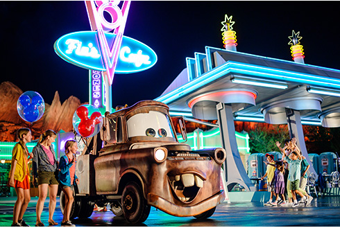 Showing slide 6 of 16 in image gallery, Three guests outside at Cars Land, Disneyland Resort in California