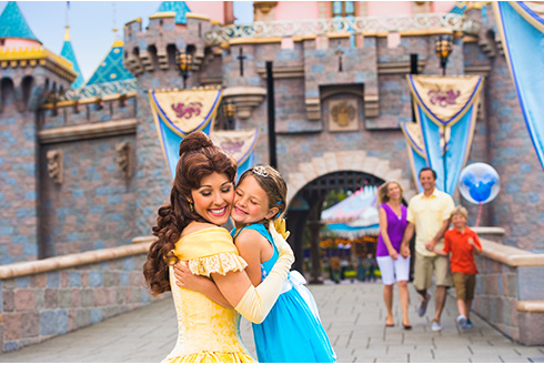 Showing slide 9 of 16 in image gallery, Belle with a guest smiling outside the Sleeping Beauty Castle