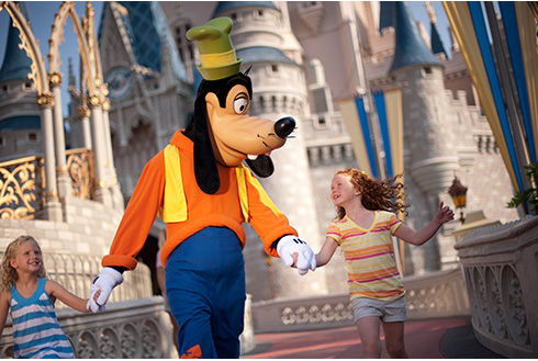 Showing slide 13 of 20 in image gallery, Goofy walking with two guests in front of the Magic Kingdom