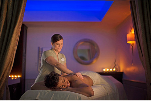 Showing slide 10 of 20 in image gallery, A woman enjoying a massage at a Walt Disney World spa