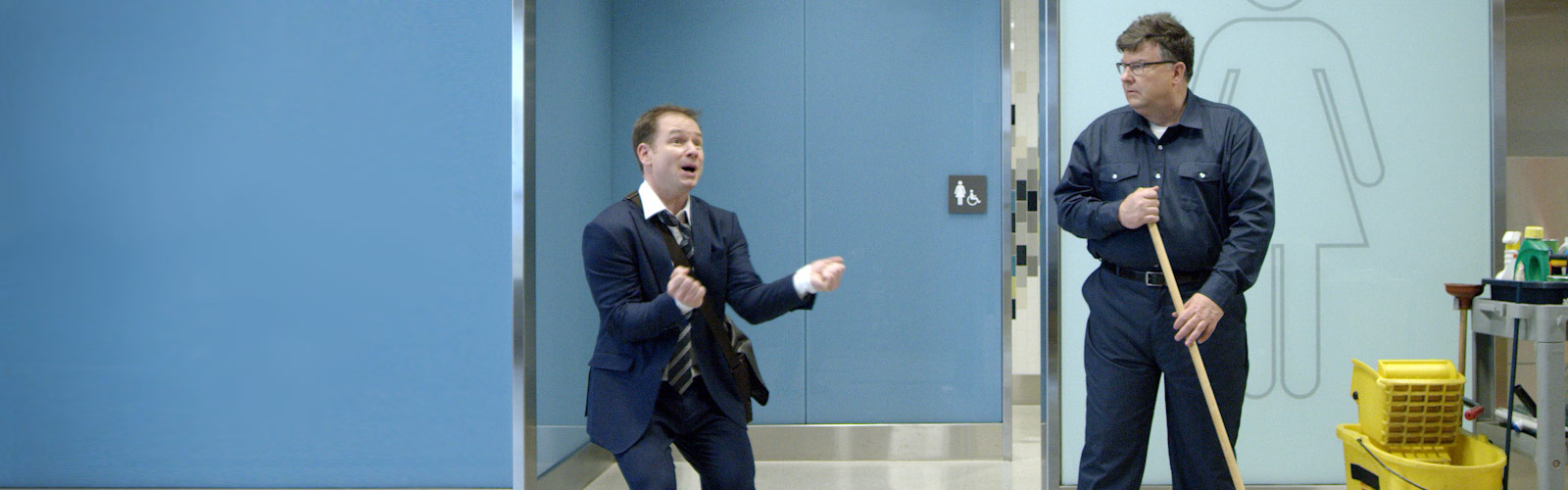 business traveler dancing in front of a custodian in an airport.