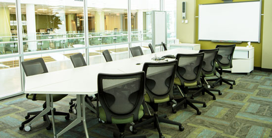 Long table with chairs facing SMART board in executive boardroom