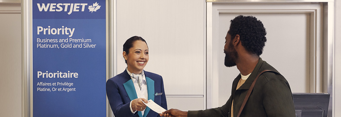Women at service desk hands man a boarding pass