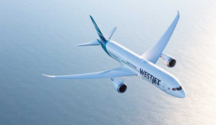 WestJet flight over water at sunset
