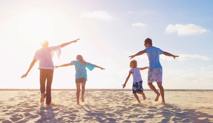 Family with children running on a sunny beach