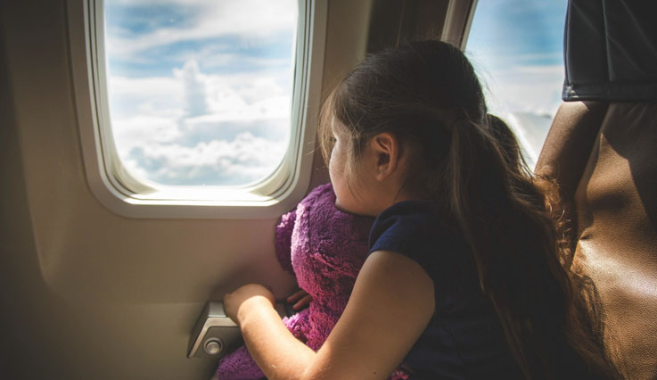 Child looking out the plane window holding a teddy bear