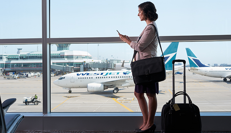 Business woman at the airport walking past WestJet plane beyond the window