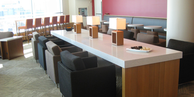 Comfortable seating at a long table in the Plaza Premium Lounge in YYZ