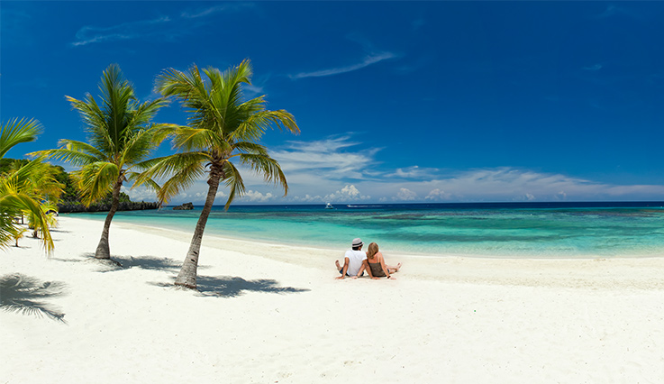 Man and woman looking at ocean while sitting on white sand beach