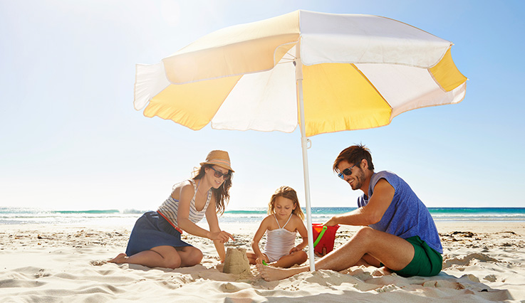 Family on a sunny beach sitting underneath a beach umbrella