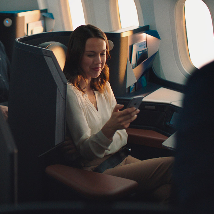 Mother sitting in business cabin on flight home