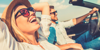 Man and woman enjoying sunny drive in convertible car