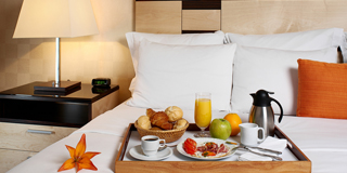 Breakfast tray on bed in hotel room