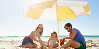 Family building sandcastle on beach under white and yellow umbrella