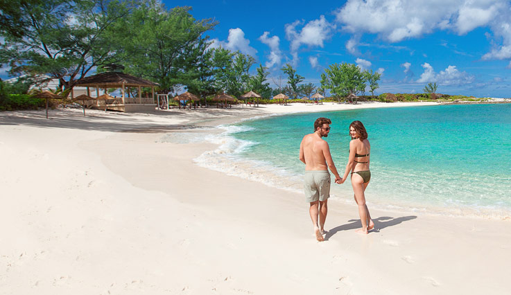 Couple walking along a white sand beach