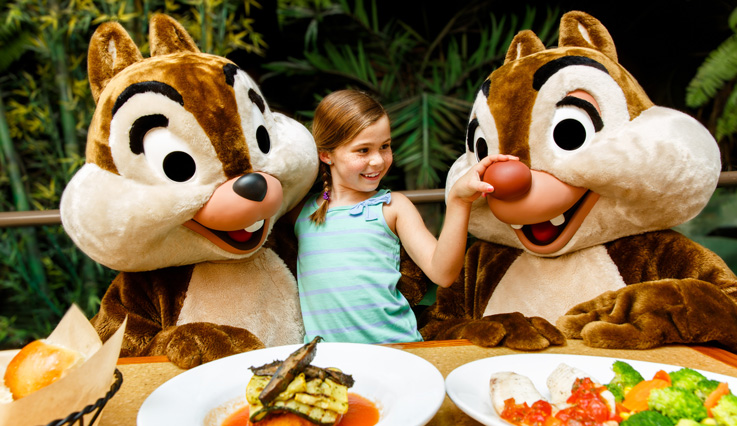 Girl shares a meal with Disney characters Chip and Dale.