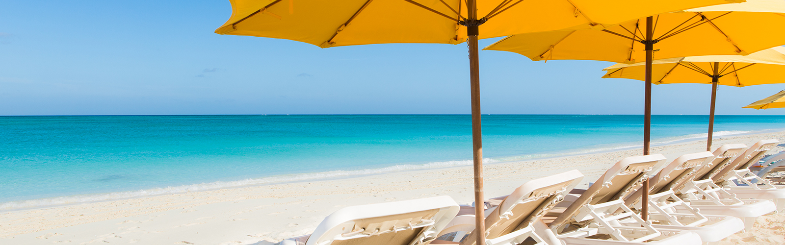 pool chairs and umbrellas along white sand and ocean