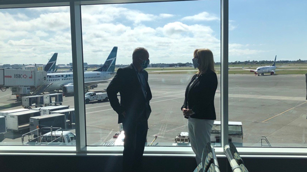 Ed and Tamara standing in front of the windows in the YVR boarding lounge with WestJet aircraft on the tarmac