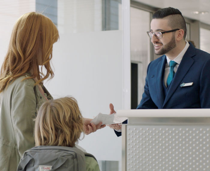 Mother and son handing travel documents to WestJet agent.