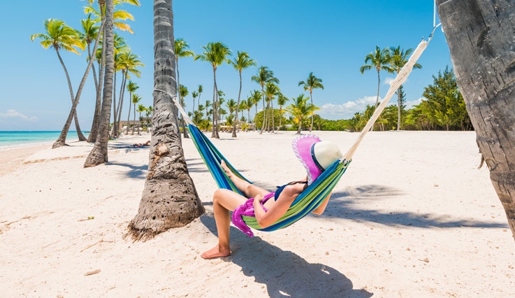 Girl sitting in hammock on a beach.