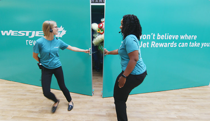 Two girls opening a giant teal-coloured box with a performance inside.
