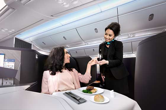 WestJet flight attendent happily serving beverage to woman in Business cabin