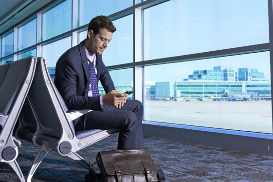 Business guest on phone sitting in airport terminal with large window facing airport taxiway