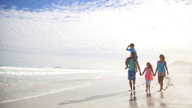 happy family walking down beach