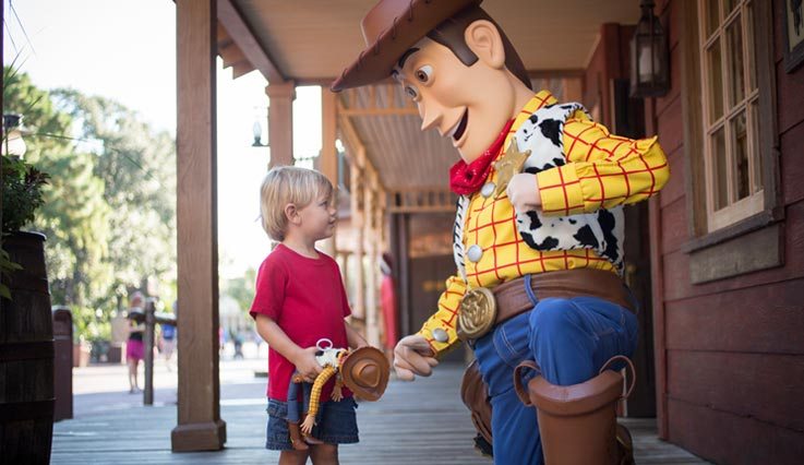 Sheriff Woody talking to boy at amusement park