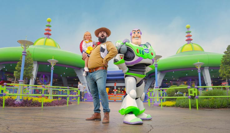 Buzz Lightyear and dad dressed as Woody in theme park