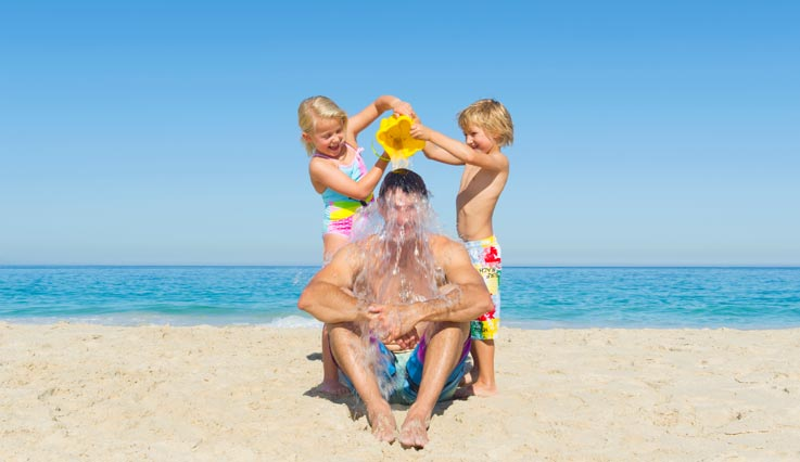 kids pouring water over dad's head on beach