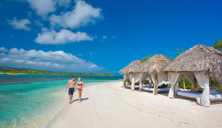 couple walking down white Caribbean beach