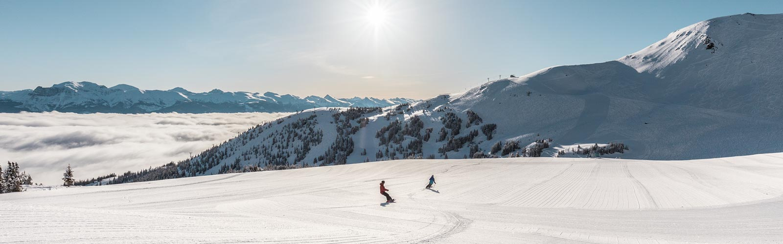 skiers on flat plain with mountain backdrop