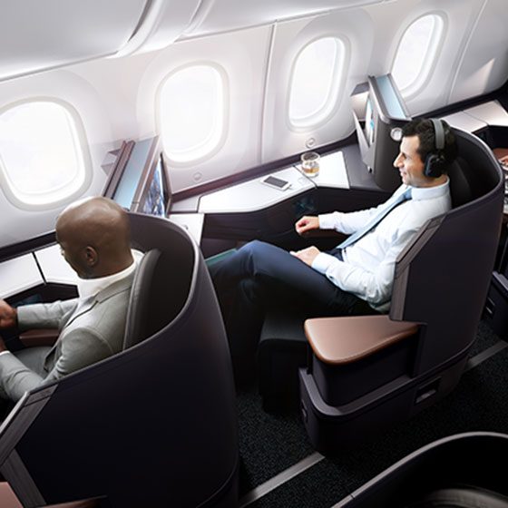 Aerial view of two guests relaxing in spacious business cabin pods on 787 Dreamliner aircraft