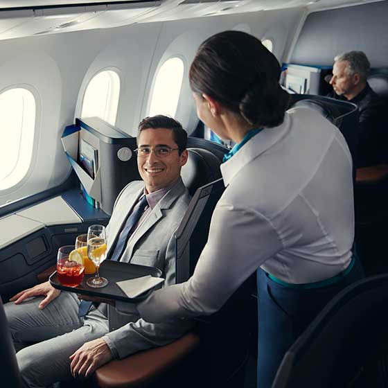 Flight attendant serving drinks to man seated in business cabin