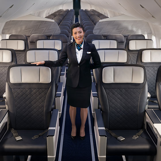 WestJet flight attendent standing in aisle of Premium cabin with 2x2 seating