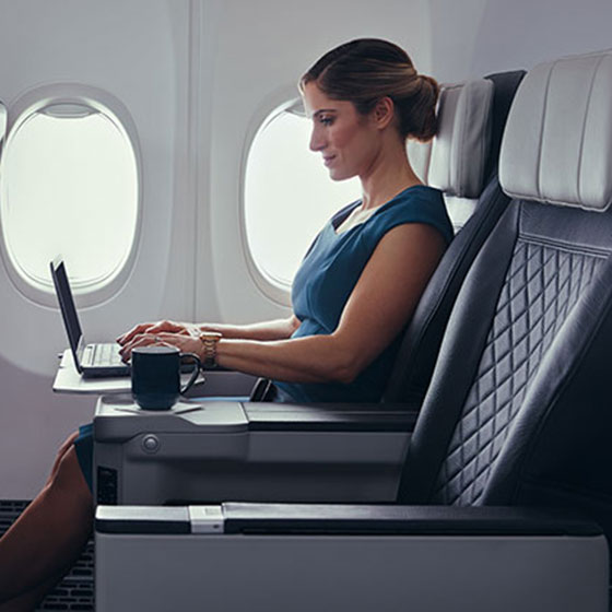Guest using laptop while inflight in premium cabin.