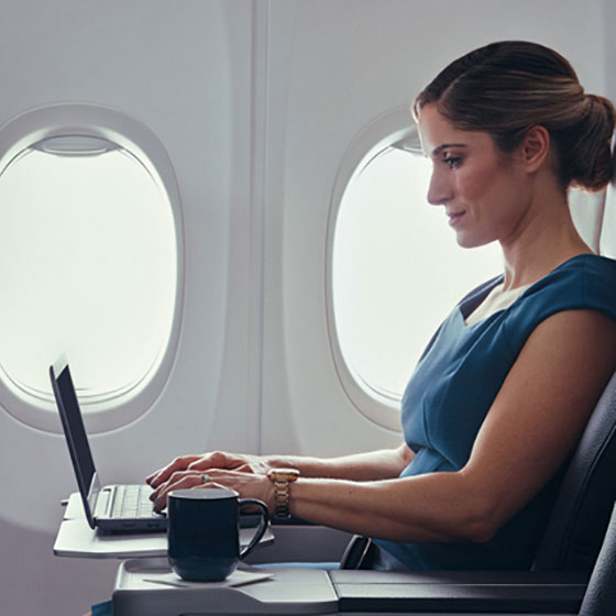 Woman on laptop in Premium cabin