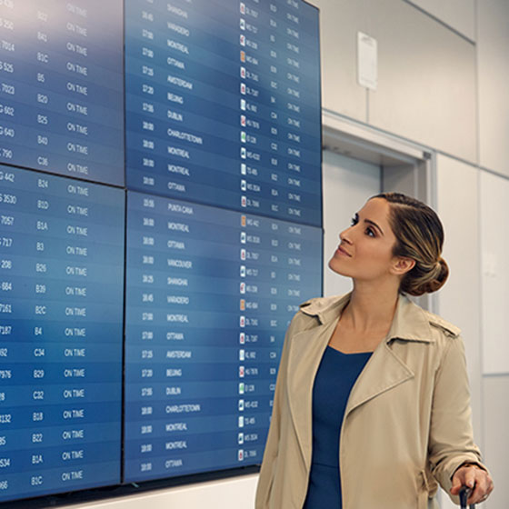 Guest reading a flight information display board at airport