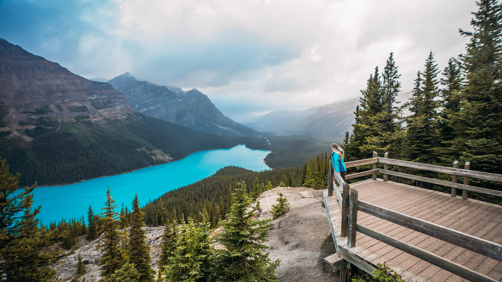 Woman on platform overlooking glacial lake and mountains