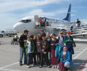 Boys and Girls club members gathered in front of Westjet aircraft